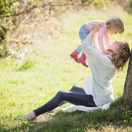 Mother holding up her daughter by a tree in the backyard.