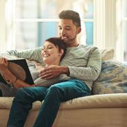Couple on the couch together reading a book.